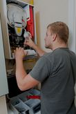 A qualified gas fitter installs a gas heater in a home